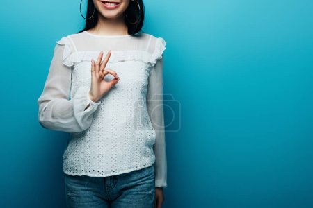 Photo for Cropped view of happy brunette asian woman showing ok sign on blue background - Royalty Free Image