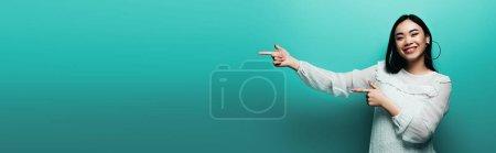 glücklich brünette asiatische Frau zeigt mit den Fingern auf türkisfarbenem Hintergrund, panoramische Aufnahme