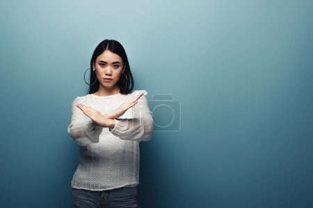 Foto de Molesto morena asiática mujer mostrando stop gesto en azul fondo - Imagen libre de derechos