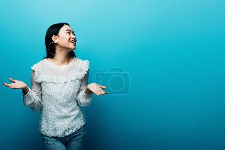 Photo pour Heureux brunette asiatique femme montrant haussement d'épaules geste sur fond bleu - image libre de droit