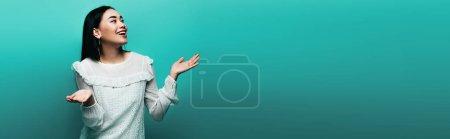 Photo pour Heureux brunette asiatique femme montrant haussement d'épaules geste sur turquoise fond, panoramique coup - image libre de droit