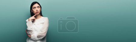 Photo for Thoughtful brunette asian woman looking away on green background, panoramic shot - Royalty Free Image
