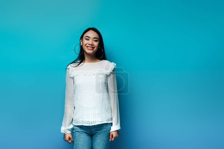 Photo for Happy brunette asian woman on blue background - Royalty Free Image