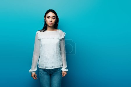 Photo for Serious brunette asian woman on blue background - Royalty Free Image