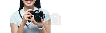 Photo pour Vue en coupe d'une femme asiatique souriante prenant une photo sur un appareil photo numérique isolée sur une photo panoramique blanche - image libre de droit