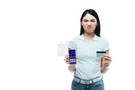 Photo for Displeased brunette asian girl holding credit card and smartphone with healthcare app isolated on white - Royalty Free Image