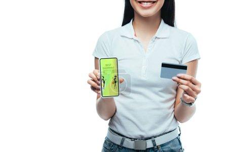 Foto de Vistas rotas de una chica asiática morena sonriente con tarjeta de crédito y teléfono inteligente con la mejor aplicación de compras aislada en blanco. - Imagen libre de derechos