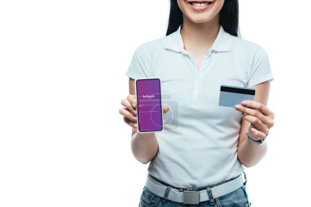 Photo pour Kyiv, Ukraine - July 15, 2019 : cropped view of smiling brunette asian girl holding credit card and smartphone with Instagram app isolated on white - image libre de droit