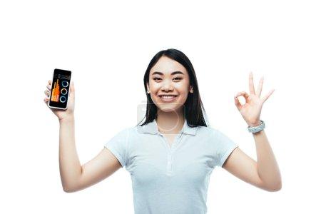 feliz morena asiática mujer sosteniendo smartphone con aplicación de negocios y mostrando ok signo aislado en blanco