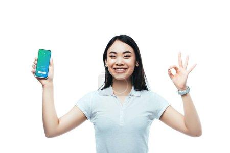 Photo pour KYIV, UKRAINE - 15 JUILLET 2019 : femme asiatique brune heureuse tenant smartphone avec application twitter et montrant ok signe isolé sur blanc - image libre de droit
