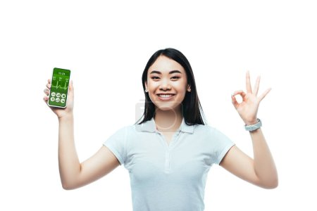 Photo for Happy brunette asian woman holding smartphone with healthcare app and showing ok sign isolated on white - Royalty Free Image