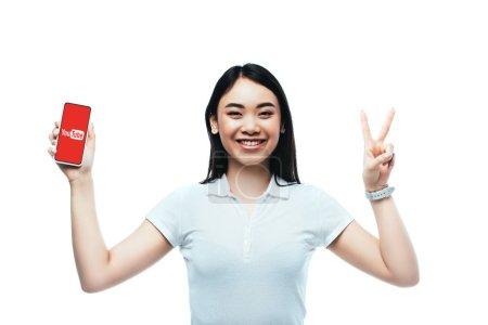 Photo pour KYIV, UKRAINE - 15 JUILLET 2019 : femme asiatique brune heureuse tenant smartphone avec application youtube et montrant signe de paix isolé sur blanc - image libre de droit