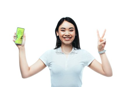 Photo pour Happy brunette asian woman holding smartphone with best shopping app and showing peace sign isolated on white - image libre de droit