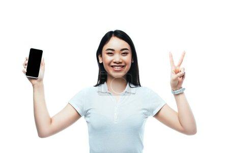 Photo pour Heureux brunette asiatique femme tenant smartphone avec écran vide et montrant signe de paix isolé sur blanc - image libre de droit