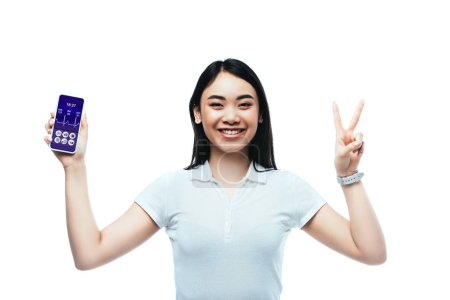 Photo for Happy brunette asian woman holding smartphone with healthcare app and showing peace sign isolated on white - Royalty Free Image