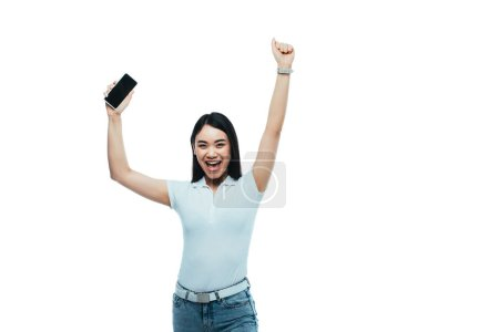 happy brunette asian woman holding smartphone with blank screen isolated on white