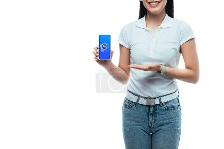 Photo pour KYIV, UKRAINE - 15 JUILLET 2019 : vue recadrée de femme asiatique brune heureuse présentant smartphone avec application shazam isolé sur blanc - image libre de droit