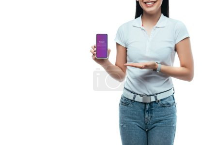 Photo for KYIV, UKRAINE - JULY 15, 2019: cropped view of happy brunette asian woman presenting smartphone with instagram app isolated on white - Royalty Free Image