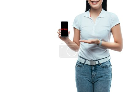 Photo for KYIV, UKRAINE - JULY 15, 2019: cropped view of happy brunette asian woman presenting smartphone with netflix app isolated on white - Royalty Free Image