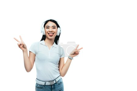 Photo pour Happy attractive asian girl in headphones showing peace signs and language isolated on white - image libre de droit