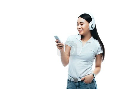 smiling attractive asian girl in headphones using smartphone isolated on white