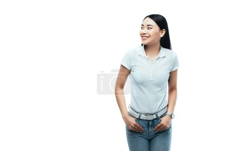 Photo for Happy attractive asian girl with hands in pockets looking away isolated on white - Royalty Free Image