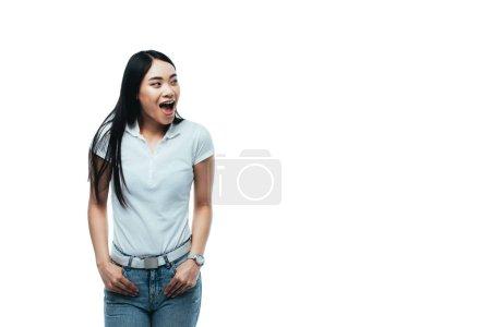Photo pour Excité attrayant asiatique fille avec les mains dans les poches et bouche ouverte regardant loin isolé sur blanc - image libre de droit