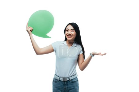 happy attractive asian girl holding green blank speech bubble isolated on white