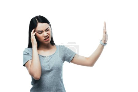 Photo pour Attractive asian girl suffering from headache and showing stop gesture isolated on white - image libre de droit