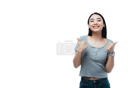 Foto de Feliz chica asiática atractiva mostrando pulgares aislados sobre blanco - Imagen libre de derechos