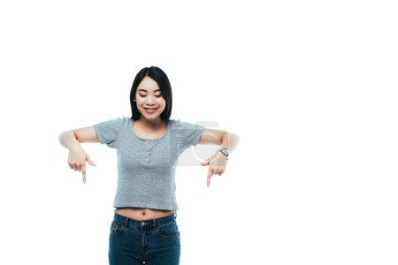 Foto de Jovencita asiática feliz que apunta con los dedos hacia abajo aislados sobre blanco - Imagen libre de derechos