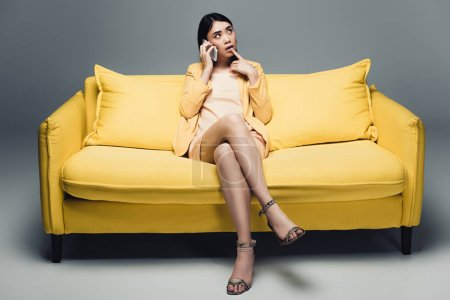 Photo for Pensive asian businesswoman sitting on yellow sofa with crossed legs and talking on smartphone on grey background - Royalty Free Image