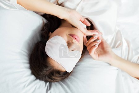 Photo for High angle view of woman in sleeping mask lying in bed at morning - Royalty Free Image