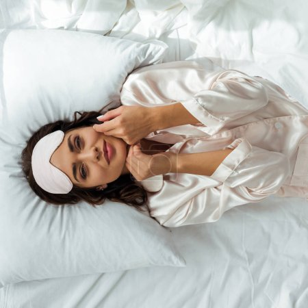 Photo for Top view of attractive woman in sleeping mask lying in bed at morning - Royalty Free Image