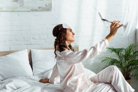 Photo for Attractive woman with sleeping mask looking at mirror at morning - Royalty Free Image
