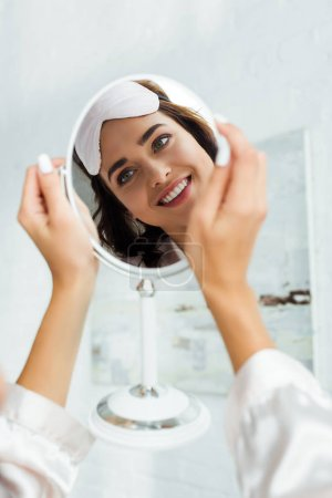 Photo for Reflection of attractive woman with sleeping mask looking at mirror at morning - Royalty Free Image