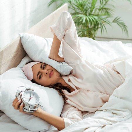 Photo pour Femme en colère masquée tenant un réveil le matin - image libre de droit