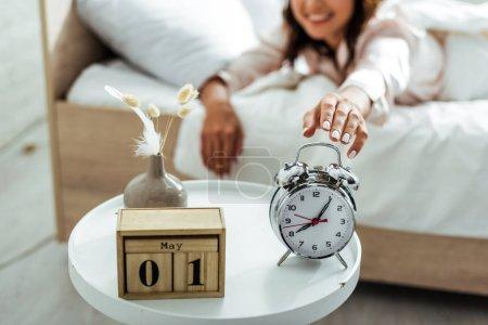 Photo pour Foyer sélectif de la femme souriante prenant réveil le matin - image libre de droit