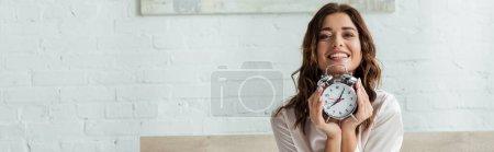 Photo pour Plan panoramique de femme attrayante souriant et tenant réveil le matin - image libre de droit
