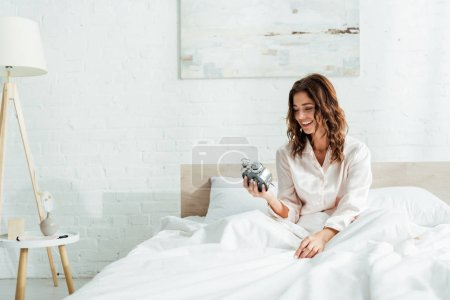 Photo for Attractive woman smiling and holding alarm clock at morning - Royalty Free Image