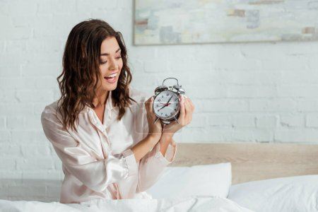 attractive woman smiling and holding alarm clock at morning