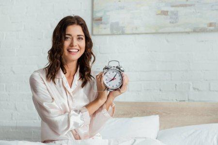 Photo pour Attrayant femme souriant et tenant réveil le matin - image libre de droit