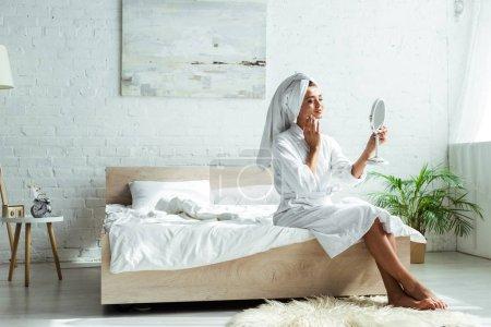 attraktive Frau in Bademantel und Handtuch, die morgens in den Spiegel schaut