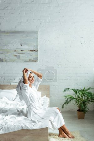 Photo for Attractive woman in bathrobe and towel smiling and sitting on bed at morning - Royalty Free Image