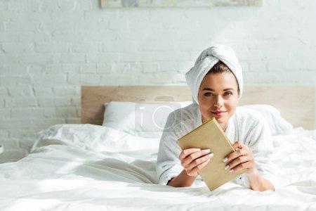 Photo pour Séduisante femme en serviette et peignoir tenant livre le matin - image libre de droit