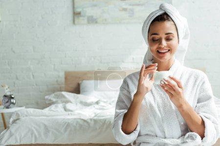 Photo pour Séduisante femme en peignoir et serviette souriante et tenant crème cosmétique le matin - image libre de droit