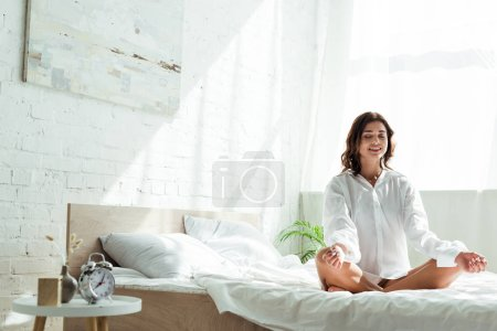 attractive woman in white shirt smiling in lotus pose at morning