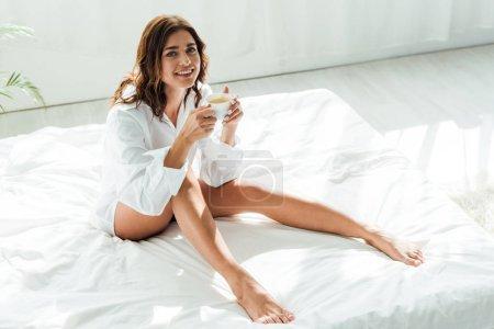 Photo pour Jolie femme en chemise blanche souriant et tenant tasse le matin - image libre de droit