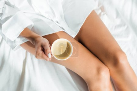 cropped view of woman holding cup of coffee at morning