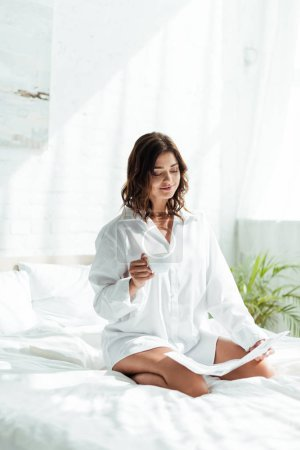 attractive woman in white shirt holding cup of coffee and reading newspaper at morning